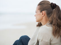 Young woman sitting on lonely beach and looking into distance Royalty Free Stock Photos