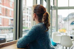 Young woman sitting looking out the window Royalty Free Stock Photography