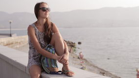 Young woman sitting and looking on the sea stock video