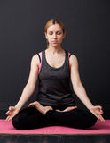 Young woman is sitting in the lotus pose with closed eyes Royalty Free Stock Photography