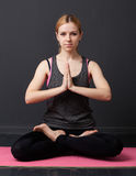 Young woman is sitting in the lotus pose, hands are joined toget Stock Image