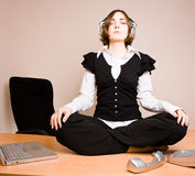 Young woman sitting in lotus pose with headphones Stock Images