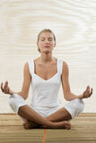 Young woman sitting in lotus position Stock Images