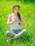 Young woman sitting in a lotus position. Royalty Free Stock Images