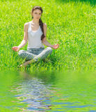 Young woman sitting in a lotus position. Stock Photos