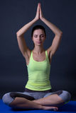 Young woman sitting in lotus position over grey Royalty Free Stock Photos
