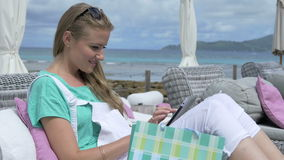 Young woman sitting in lounger using digital tablet during vacation. Young blonde woman reading e-book in tropical resort. Woman relaxing with tablet computer stock footage