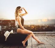 Young woman sitting on luggage waiting to go for a vacation stock photos
