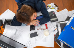 Young woman sitting and lying asleep over office desk with papers, calculator, pens, computer keyboard Royalty Free Stock Photo