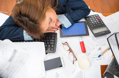 Young woman sitting and lying asleep over office desk with papers, calculator, pens, computer keyboard Stock Photo