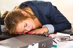 Young woman sitting and lying asleep over office desk with papers, calculator, pens, computer keyboard Royalty Free Stock Photos