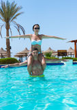Young woman sitting on man`s neck while they doing aqua fitness. Young women sitting on man`s neck while they doing aqua fitness in swimming pool at the hotel on Stock Images