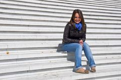 Young woman sitting on the marble steps Royalty Free Stock Image