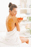Young woman sitting on massage table with honey plate Royalty Free Stock Images