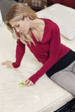 Young woman sitting mattress while looking at price tag Stock Photo