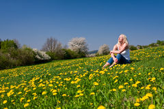 Young woman sitting on a meadow Stock Images