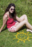 Young woman sitting on a meadow close to yellow flowers in a shape of sun Stock Photo