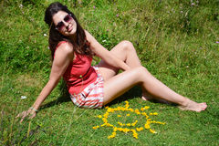 Young woman sitting on a meadow close to yellow flowers in a shape of sun Royalty Free Stock Photos