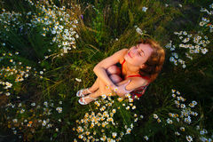 Young woman sitting in meadow with daisies top view Royalty Free Stock Photos