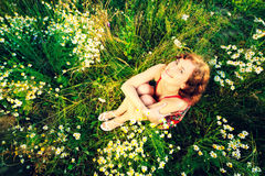 Young woman sitting in meadow with daisies top view Royalty Free Stock Images
