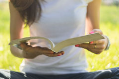 Young woman sitting on a meadow and holding an open book Royalty Free Stock Photo