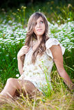 Young woman sitting on meadow and touching her long hair Royalty Free Stock Image