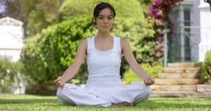 Young woman sitting meditating in a garden stock video