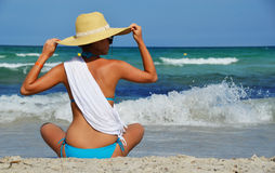 Young woman sitting on the mediterranean beach on hot summer day Royalty Free Stock Images