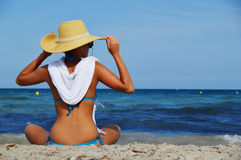 Young woman sitting on the mediterranean beach on hot summer day Stock Photography