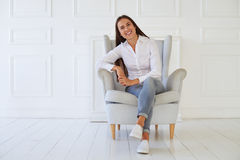 Young woman sitting in a modern armchair relaxing in her room Royalty Free Stock Photography