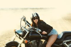 Young woman on a motorcycle on a summer day stock photography