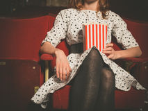 Young woman sitting in movie theater with popcorn. A young woman is sitting in a movie theater with a bucket of popcorn Royalty Free Stock Image
