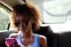Young woman sitting n backseat of car looking at cell phone Stock Image