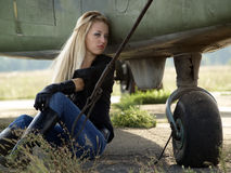 Young woman sitting near airplane Stock Photos