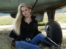 Young woman sitting near airplane Stock Image
