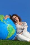 Young woman sitting near big globe Royalty Free Stock Photography