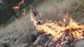 Young Woman Sitting Near Campfire stock footage