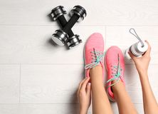 Young woman sitting near dumbbells on floor,. Flat lay. Ready for gym workout stock images
