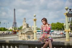 Young woman sitting near the Eiffel tower in Paris royalty free stock image