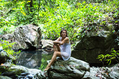 Young  woman sitting near the forest pond. Royalty Free Stock Photo