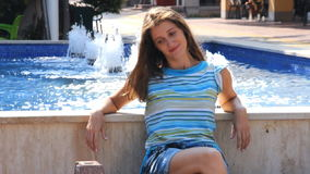 Young woman is sitting near fountain stock footage
