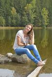 Young woman sitting near a lake. Royalty Free Stock Photo