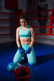 Young woman sitting near lying boxing gloves and helmet in ring Stock Photo