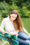 Young woman sitting near pond and reading book Royalty Free Stock Images