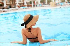 Young woman sitting near the pool. Sexy girl with healthy tanned skin. Female with sun hat relaxing in swimming pool. Water in resort spa hotel on travel royalty free stock images