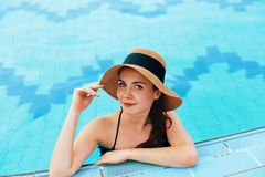 Young Woman Sitting Near The Pool. Sexy Girl With Healthy Tanned Skin. Female With Sun Hat Relaxing In Swimming Pool Royalty Free Stock Photography