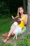 Young woman sitting near a tree,reading a book. Young woman sitting near the tree and reading a book in a garden Royalty Free Stock Photo