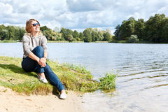 Young woman sitting near water Stock Images