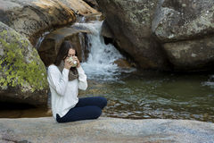 Young woman sitting near the waterfall and drinking tea, surroun Royalty Free Stock Photos