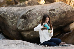 Young woman sitting near the waterfall, with a thermos, and maki Stock Photography